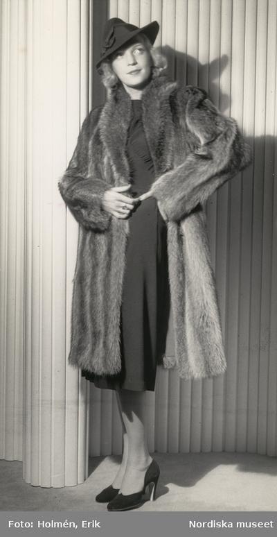 Nordiska Kompaniet. Kvinna i skiftande pälskappa och svart hatt.