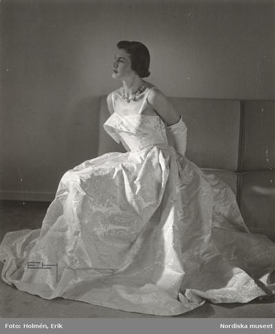 Nordiska Kompaniet. Kvinna i ljus, mönstrad aftonklänning med smala axelband. Omlottdraperin vid bysten. Text på baksidan: