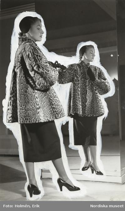 Nordiska Kompaniet. Kvinna framför en spegel i höftlång, vid pälskappa av ozelot. Mörk kjol, mörk hatt. Text på baksidan: