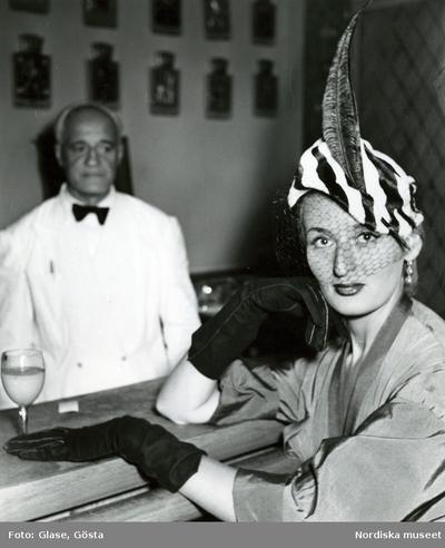 Kvinna i zebramönstrad hatt med flor och fjäderpenna i en bar. Servitör  bakom bardisken. 8685e00cdc933