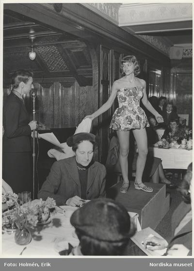 Tonårsmodevisning, Vår. Modell i mönstrad kortkort klänning och sandaler. Kvinna vid mikrofon och publik vid bord.
