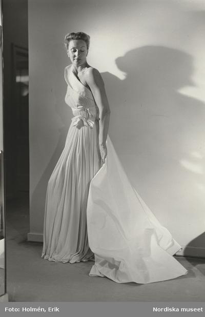 Modell i aftonklänning med släp och rosetter. NK s Franska efter Madame  Grès. 0838692d521f7