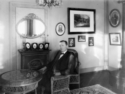 Godseier Valheim sittende i kurvstol foran kaminen i havestuen på Elingaard