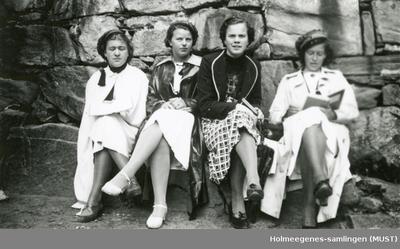 Fire jenter med russelue sitter ved en steinmur