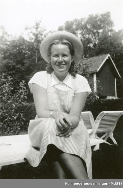 En ung kvinne med hatt sitter på et hagebord