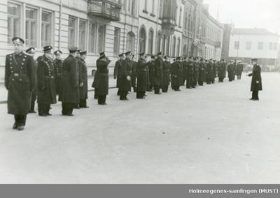 Politifolk oppstilt på rekke og rad foran en bygning