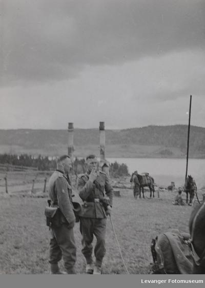 To tyske soldater røyker med hester i bakgrunnen