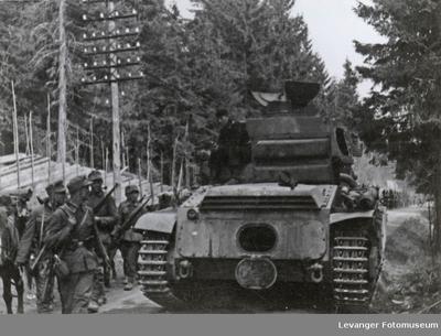 Stridsvogn og marsjerende soldater i en fremrykking