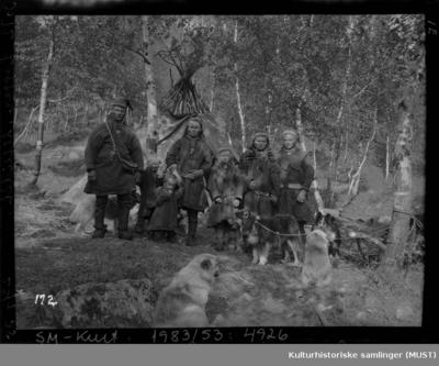 Samer i samedrakter og hunder foran en lavvo