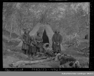 En samekvinne med fire barn og en hund foran en lavvo i Alteidet