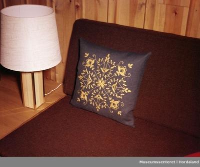 1643f9a2 Reklamefoto av brodert pute i interiør