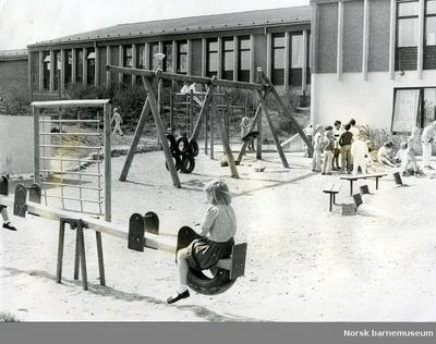 Vippe, klatrestativ og barn i skolegård