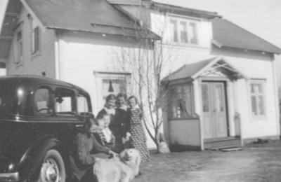 Damer og menn som står ved siden av en bil