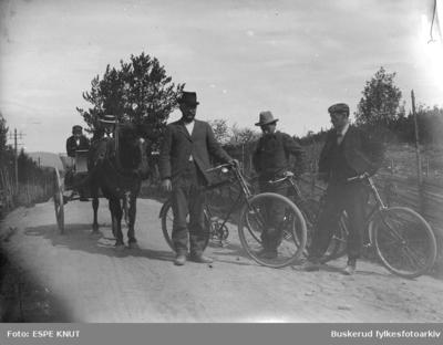 Tre menn på sykkel sammen med personer til hest