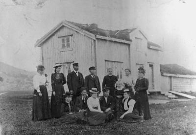 Gruppebilde foran et toetasjes hus med torvtak