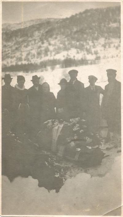 En gruppe mennesker ved ei kiste under en begravelse
