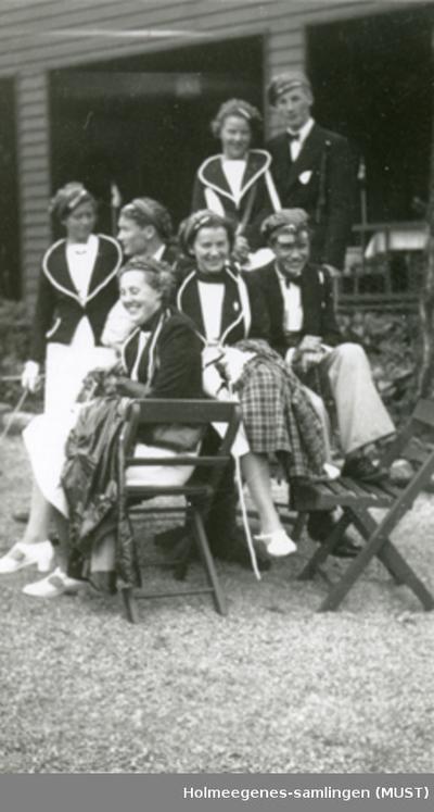 Fire jenter og tre gutter i russedrakter sitter utenfor en bygning