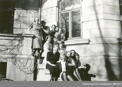 11 kvinner på en balkong/trapp