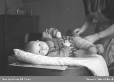 Arne Jacobsen blir stelt av sin mor Aase Jacobsen og ligger på en lys dyne/pledd som er lagt på bordet