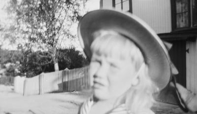 Iacob med sommerhatt på hodet fotografert på gårdsplassen utenfor et hus