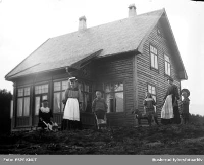 Gruppe bestående av fire barn med leker og to kvinner