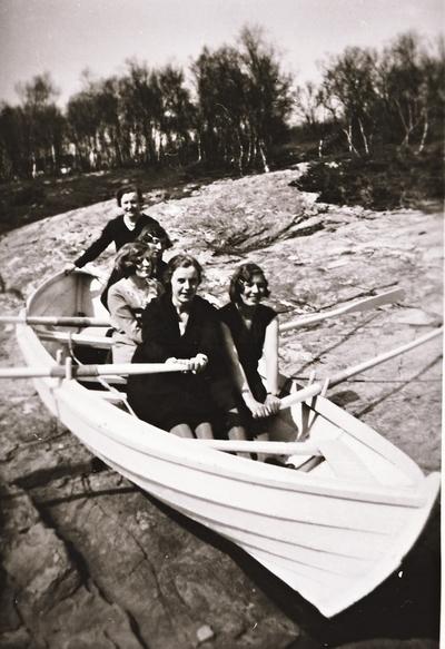 Fem damer i båt på land