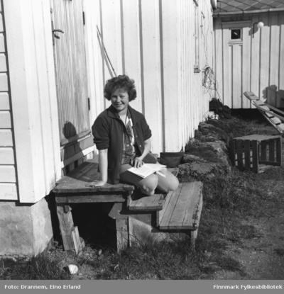 Turid Karikoski sitter på en trapp og leser i solskinnet