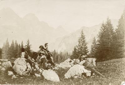 4 menn poserer for fotografen i Alpe-landskap