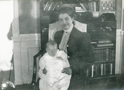 Leonie Petersson med sonen Klaus i dåpskjole framfor bokreolen
