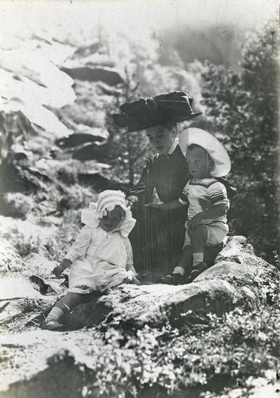 Kvinne og to små born i eit solfyllt terreng