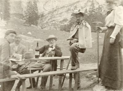 Menn og ei kvinne rastar på tur i Alpe-landskap