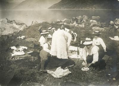 Menn og kvinner på picknick ved ein fjord