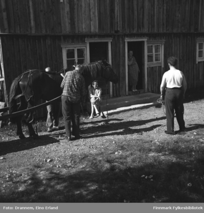 Fem personer og en hest fotografert utenfor en stor driftsbygning
