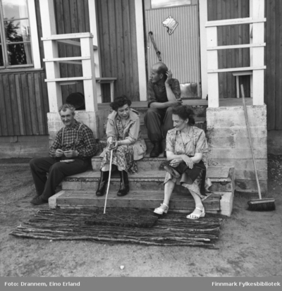 Fire personer sitter på trappa til grensevaktstasjonen på finsk side i Neiden