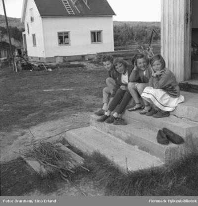 Fire jenter sitter på en betongtrapp i Neiden