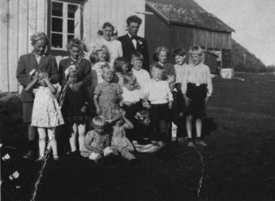 Brudepar og mange unger foran et hus i Vassvika