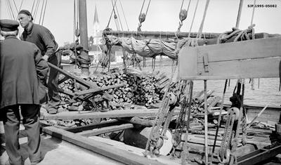 Lessing av ved i seilskute i havneområdet i Lillesand i Aust-Agder sommeren 1935