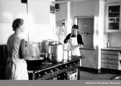 Foto av to kokker i aksjon på et storkjøkken i Kristiansund under gjenreisningsperioden like etter krigen