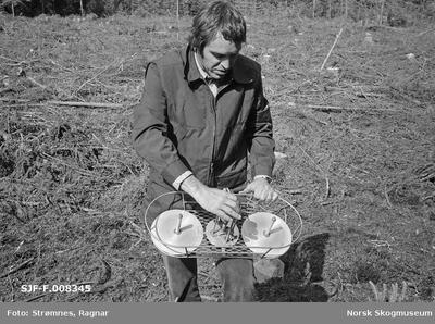 «Konsulent Olav Kaveldiget demonstrerer planting. Juni 1977»«Torvbrikettplanter og Ulvins planteutstyr»