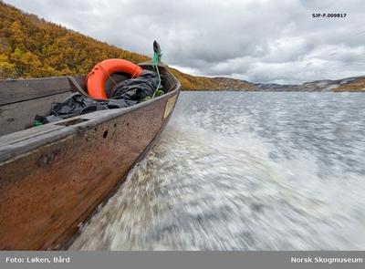 Elvebåt med påhengsmotor i full fart på Kautokeinoelva/Guovdageaineatnu i Finnmark