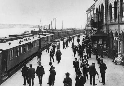Drammen jernbanestasjon med flere tog og mange reisende på plattformen