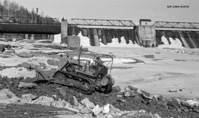 Bulldoserarbeid etter sprenging av en bergnabb ved Glommas nordvestre bredd like nedenfor kraftstasjonen ved Rånåsfoss i Sørum kommune på Romerike