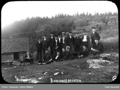 En gruppe menn og ungdommer hviler på gressbakken på Blankvannsbråten
