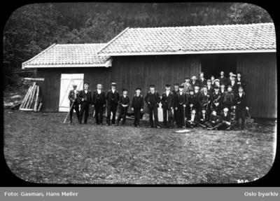 En gruppe menn og ungdommer i penklær poserer for fotografen foran et uthus eller låve