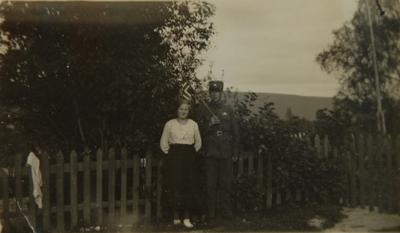 Ung kvinne og ung mann med flagg foran et stakittgjerde