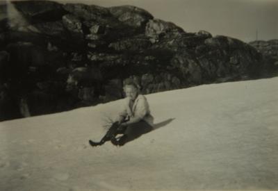 Kvinne sitter på snø