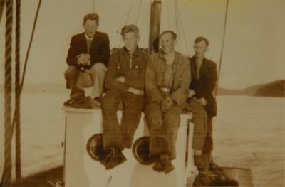 Fire menn poserer på styrhuset på en fiskebåt