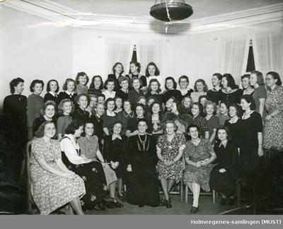 Innendørs gruppeportrett av rundt 50 kvinner stående/sittende