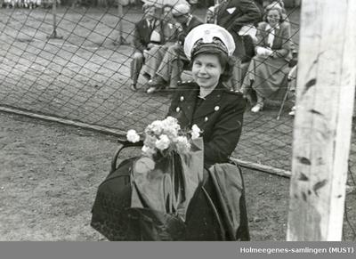 Utendørs foto av kvinne i politiuniform sittende med blomsterbukett i armene