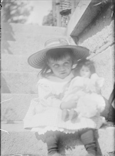 En liten jente sitter i en steintrapp og i armene holder hun dukken sin